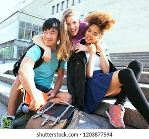 cute group teenages at the building of university with books huggings, back to school