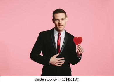 cute guy in black suit holding red heart on pink background