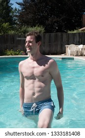 Cute guy getting out of a swimming pool on a hot day. Young white man waist deep in water in an outdoor swimming pool in the summer, no shirt, looking to the side.