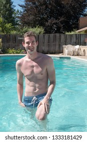 Cute guy getting out of a swimming pool on a hot day. Young white man waist deep in water in an outdoor swimming pool in the summer, no shirt, looking at the camera smiling, hand on leg.