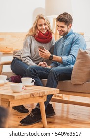 Cute guy and girl using smartphone for fun