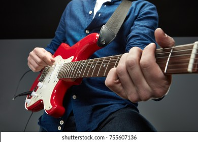Cute guy playing the guitar. Studio portrait.