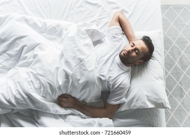 Cute guy slumbering on comfortable bedding
