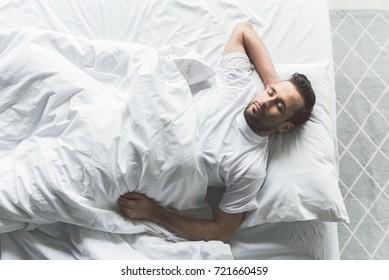 Cute guy slumbering on comfortable bedding