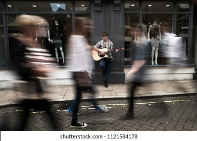 Cute guy standing playing acoustic guitar as blurred people walk by in the town of Colchester, Essex