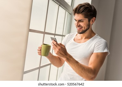 Cute guy using mobile phone at home