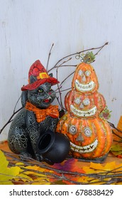 Cute halloween decorations including cauldrons, a cat, a stack of pumpkins, bare twigs and autumn leaves in front of a rustic white-washed wooden background