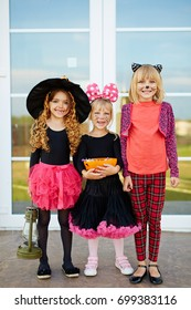 Cute halloween girls with treats standing by door outside
