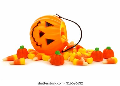 Cute Halloween Jack o Lantern candy collector with spilling candy pumpkins and candy corn over white
