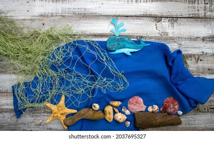 Cute handcrafted whale or sperm whale and fishing net on rough vintage wooden background top view conceptual image