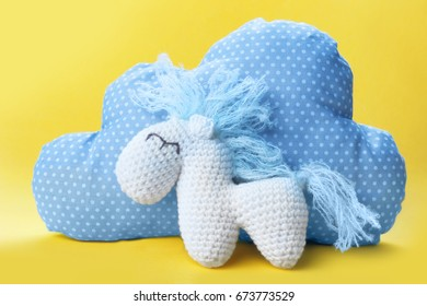 Cute handmade horse toy with pillow in shape of cloud on color background, closeup