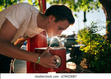 Cute handsome american young hipster teenager man in white tshirt drinks water from street fountain, with beautiful shadow sun light leaks beaming on drops, healthy hydration