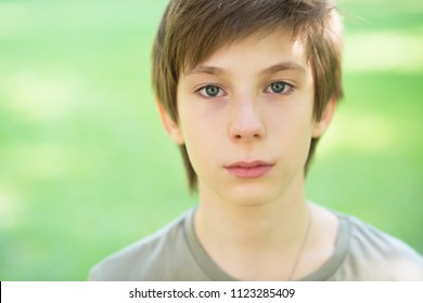 Cute handsome boy is crying outdoor. Sad early teen boy in summer park.