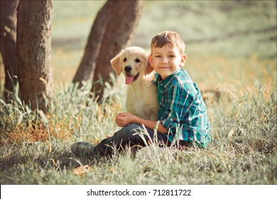 Cute handsome boy teen with blue eyes playing outdoor amazing white pink labrador retriever puppy enjoying summer sunny day vacation weekend with full happyness.Happy smiling kid with best friend