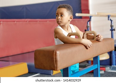 Cute handsome dark skinned schoolboy exercising on pommel horse with brown leather cover. Portrait of African child using artistic gymnastics apparatus at gym. Childhood, activity and sports