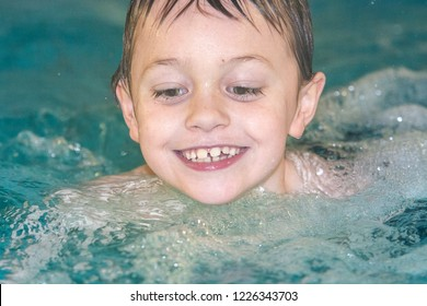 A cute, handsome little boy with ADHD, Autism, Aspergers syndrome swimming laughing and having fun in the pool