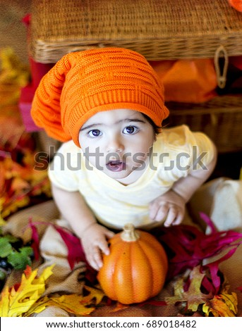 9432fc4e2c0 Cute handsome little boy dark eye sitting and looking in camera with a  pumpkin in yellow t-shirt and orange long knit hat fall autumn leaves -  Image