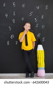 Cute handsome school boy in yellow t-shirt tie and stylish boots casuals standing close to black board with numbers and holding huge big soft toy pencil and smiling.