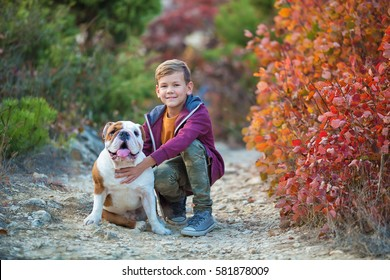 Cute handsome stylish boy enjoying colourful autumn park with his best friend red and white english bull dog.Delightfull scene of pretty boy together with bulldog in forest. Young teenager smiling .