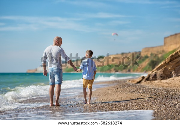 Cute handsome stylish dressed boy with father dad in light blue shirt and yellow shorts walking on sea side rocky beach and enjoying delightful nature.Happy life of smiling teenager in country side.
