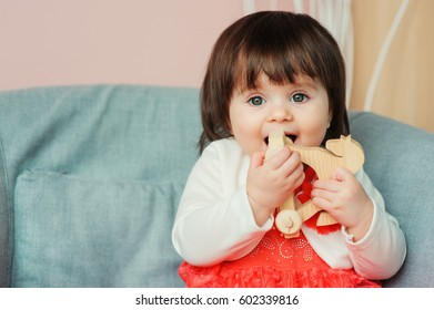 cute happy 1 year old baby girl playing with wooden toys at home. Modern nursery interior, early learning concept