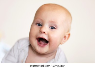A cute, happy 5 month old baby girl is smiling a toothless grin at the camera on a white background.