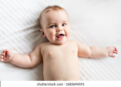 A Cute happy 7 month baby girl lying on bed