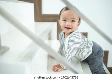 Cute happy Asian 10 months old toddler baby girl child climbing up stairs at home alone, Looking and smiling at camera, Movement, Balance & Coordination, Stair climbing developmental milestone concept