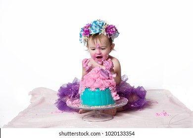 Cute happy baby girl with blue eyes is tasting the  cake and purple butter icing on her sticky fingers from her first birthday cake smash while sitting on a white background