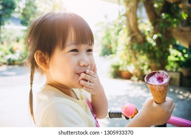 Cute happy baby girl are eating ice cream in summer. Picture for concept of sweet ,fat ,obesity and diabetes in children.