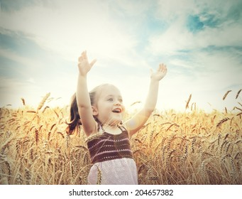 Cute happy baby playing on wheat field