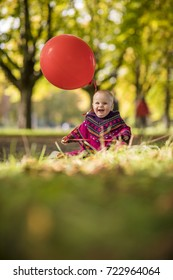 cute happy baby playing outside in autumn fall sun