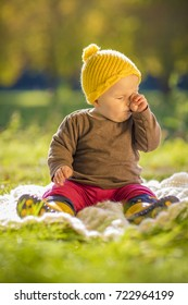 cute happy baby playing with yellow beanie hat in autumn fall sun