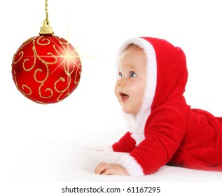 Cute happy baby in red Christmas clothes looking at sparkling red bauble decoration isolated on white