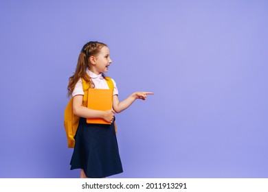 Cute happy baby in shape. he points his finger to the side on the purple background. child with backpack. the little girl is ready for school, going back to the conceptual school. the holidays begin.