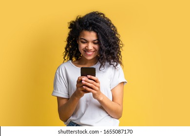 Cute happy blogger girl with perfect smile in basic white t-shirt using her mobile phone answering to her followers, texting to her boyfriend, browsing various applcations. Device addiction concept.