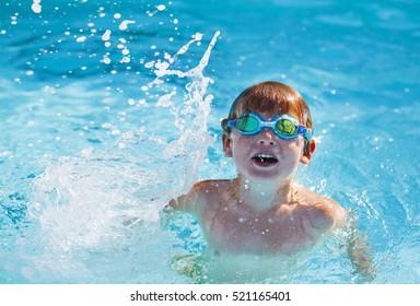 Cute happy  blond boy in goggles swimming and  splashing in water. A child swims in the pool.