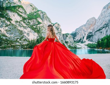 cute happy blond girl in long luxury vintage red dress silk train fly wind. Woman enjoy amazing fabulous nature. Backdrop alpine lake Braies turquoise water white mountains green forest summer nature