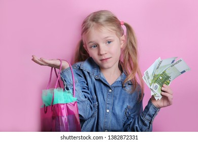 cute happy blonde little girl in jeans shirt holding euro cash money banknote and colorful shopping bag, on pink background.