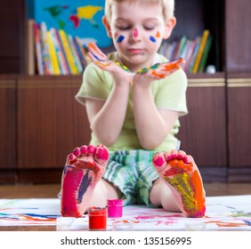 Cute happy boy with colorful  painted hands and foot