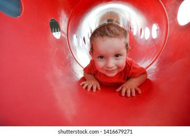 Cute happy boy crawling through tube at playground