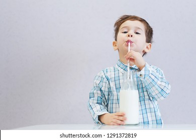 cute happy boy with dark eyes drinks milk from a bottle. the child is wearing a plaid shirt