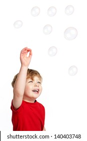 Cute Happy boy playing with bubbles shot in the studio on a white background.