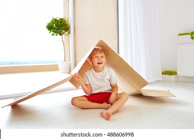 cute happy boy playing with cardboard box as with toy house