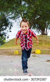 cute happy boy playing hopscotch in the park