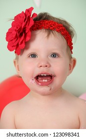 Cute happy brunette baby girl in pink tutu and red flower head band sitting on green background and vintage wooden floor by rose swirl decorated pink butter iced cake with dirty sticky hands