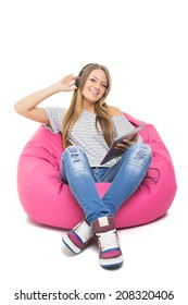 Cute happy Caucasian blonde teenage girl with headphones and tablet listening to music sitting on pink beanbag isolated on white background.
