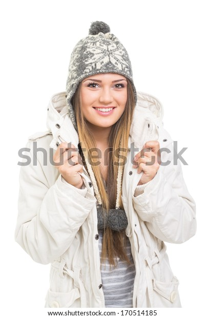 Cute happy Caucasian teenage girl in beanie hat and jacket smiling looking at camera isolated on white background. Winter fashion concept.