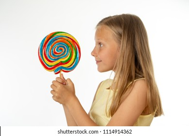 cute happy child with candy lollipop, happy girl eating big sugar lollipop, kid eat sweets. surprised child with candy. isolated on white background, studio. Beautiful little girl with lollipop