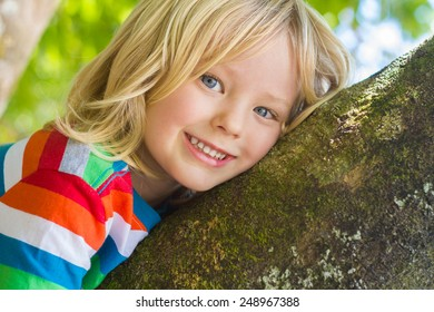 Cute happy child relaxing outdoors in a tree